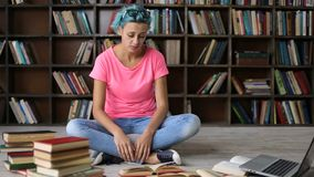 Studente frustrato che ha molto leggere dentro biblioteca stock footage