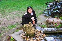 Studente graduato allegro Playing con la fontana di forma dell'elefante Immagine Stock