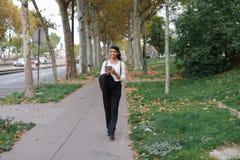 Studente grazioso afroamericano che cammina con la compressa nel parco di autunno, zaino d'uso Fotografie Stock
