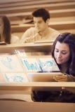 Studente grazioso che analizza i grafici sul suo calcolo futuristico della compressa Fotografia Stock