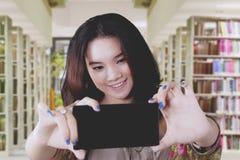 Studente grazioso che fa selfie in biblioteca Fotografia Stock