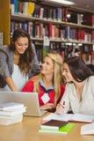Studente grazioso che mostra ai suoi compagni di classe qualcosa sul computer portatile Immagine Stock