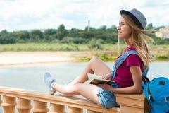 Studente grazioso che si siede con un libro vicino al fiume Immagine Stock Libera da Diritti