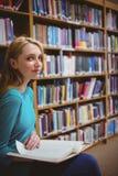 Studente grazioso che si siede sul libro della tenuta della sedia in biblioteca Fotografia Stock