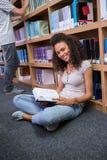 Studente grazioso che si siede sul libro di lettura del pavimento in biblioteca Fotografia Stock Libera da Diritti