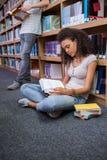 Studente grazioso che si siede sul libro di lettura del pavimento in biblioteca Immagini Stock Libere da Diritti