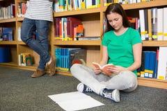 Studente grazioso che si siede sul pavimento in biblioteca Fotografie Stock Libere da Diritti