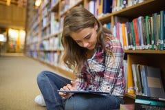 Studente grazioso che si siede sul pavimento delle biblioteche facendo uso della compressa Fotografia Stock Libera da Diritti