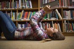 Studente grazioso che si trova sul libro di lettura del pavimento delle biblioteche Immagine Stock