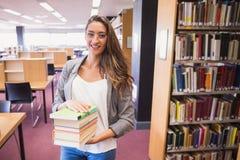 Studente grazioso che sorride alla macchina fotografica in biblioteca Fotografie Stock Libere da Diritti