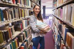 Studente grazioso che sorride alla macchina fotografica in biblioteca Fotografie Stock