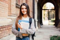 Studente grazioso che sorride alla macchina fotografica fuori sulla città universitaria all'università Fotografia Stock