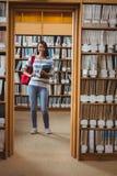 Studente grazioso che sta nella biblioteca che tiene un libro Immagine Stock