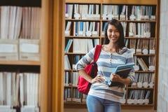 Studente grazioso che sta nella biblioteca che tiene un libro Fotografie Stock Libere da Diritti