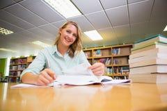 Studente grazioso che studia nella biblioteca Fotografia Stock