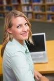 Studente grazioso che studia nella biblioteca Immagine Stock