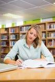 Studente grazioso che studia nella biblioteca Fotografie Stock Libere da Diritti