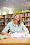 Studente grazioso che studia nella biblioteca Fotografia Stock Libera da Diritti