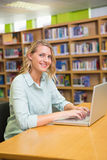 Studente grazioso che studia nella biblioteca con il computer portatile Fotografie Stock Libere da Diritti