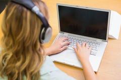 Studente grazioso che studia nella biblioteca con il computer portatile Fotografia Stock