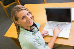 Studente grazioso che studia nella biblioteca con il computer portatile Immagini Stock Libere da Diritti