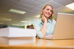 Studente grazioso che studia nella biblioteca con il computer portatile Immagine Stock