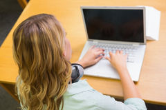 Studente grazioso che studia nella biblioteca con il computer portatile Immagine Stock Libera da Diritti