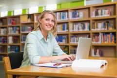 Studente grazioso che studia nella biblioteca con il computer portatile Immagini Stock