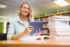 Studente grazioso che studia nella biblioteca con la compressa Immagine Stock Libera da Diritti