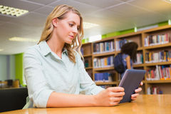 Studente grazioso che studia nella biblioteca con la compressa Immagine Stock