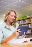 Studente grazioso che studia nella biblioteca con la compressa Fotografie Stock Libere da Diritti