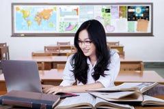 Studente grazioso che utilizza computer portatile per lo studio nella classe Fotografia Stock Libera da Diritti
