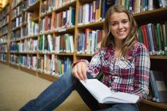 Studente grazioso felice che si siede sul libro di lettura del pavimento delle biblioteche Immagini Stock Libere da Diritti
