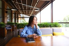 Studente grazioso femminile che si siede al caffè con il taccuino sulla tavola con lo smartphone Immagini Stock