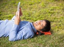 Studente Holding Book While che si trova sull'erba a Fotografia Stock
