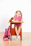 Studente: La ragazza si siede a scrittura dello scrittorio della scuola in taccuino Fotografia Stock