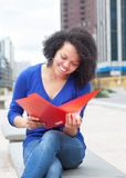 Studente latino di risata con il documento della lettura dei capelli ricci nella città Fotografie Stock