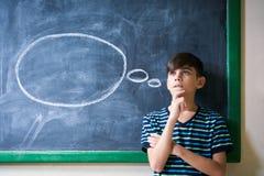 Studente Leaning On Blackboard e pensare del ragazzo alla scuola Immagini Stock
