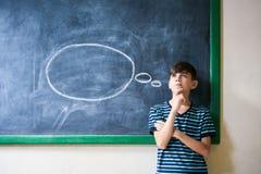 Studente Leaning On Blackboard e pensare del ragazzo in aula Fotografia Stock