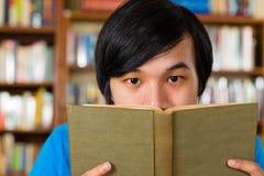 Studente in libro di lettura delle biblioteche Fotografie Stock