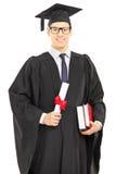 Studente maschio in abito di graduazione che posa con un diploma Fotografia Stock