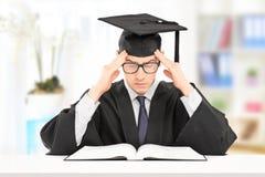 Studente maschio in abito di graduazione che studia all'interno Immagine Stock Libera da Diritti