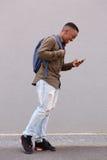 Studente maschio africano sorridente che cammina con il telefono cellulare e la borsa Fotografie Stock