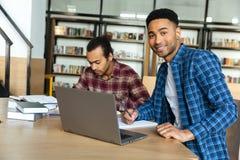 Studente maschio africano sorridente dei giovani che per mezzo del computer portatile per uno studio Fotografia Stock Libera da Diritti