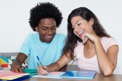 Studente maschio afroamericano che impara con lo stu femminile caucasico Immagine Stock Libera da Diritti