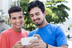 Studente maschio afroamericano con l'acconciatura tipica nei tipi ispanici di cityTwo che mostrano le immagini sul telefono Fotografie Stock Libere da Diritti