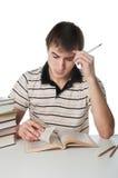 Studente maschio alla tavola con il mucchio dei libri Fotografie Stock Libere da Diritti