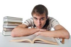 Studente maschio alla tavola con il mucchio dei libri Fotografia Stock Libera da Diritti