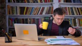 Studente maschio attraente che fa le note, facendo uso del computer portatile e studiante nella biblioteca video d archivio