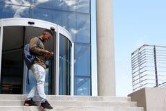 Studente maschio che cammina sulla città universitaria con il telefono cellulare Immagini Stock